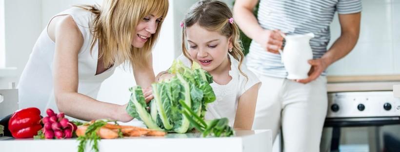 Junge Familie mit frischem Gemüse in der Küche